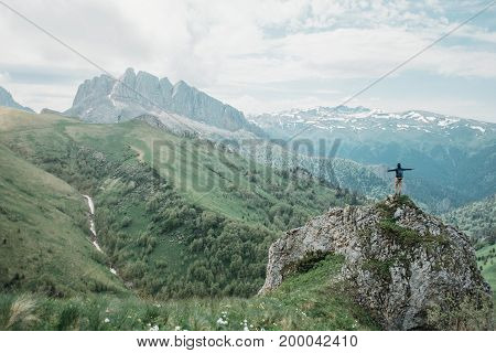 Hiker standing on peak of cliff with raised arms on background of summer mountains. Small figure of explorer on nature.