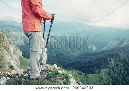 Unrecognizable female explorer with trekking poles standing on peak of mountain in summer.