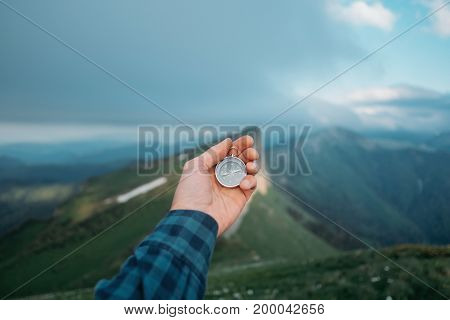 Male traveler holds a compass on background of mountains in summer view of hand pov.