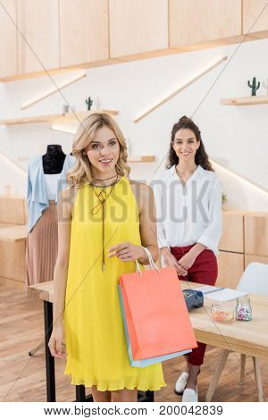 Happy Female Customer In Clothes Store Holding Shopping Bags With Cashier On Background