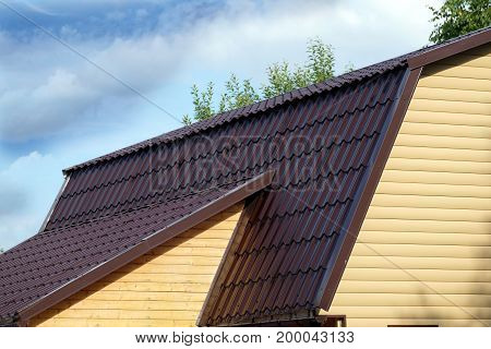 Brown metal roof of rural house covered with yellow siding over blue sky with clouds on sunny day side view
