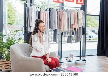 beautiful young woman talking by phone in showroom
