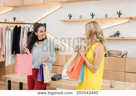 Young Beautiful Women With Colorful Bags In Clothes Store