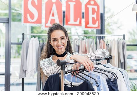 Beautiful Shopaholic Woman Leaning On Rack In Clothes Store
