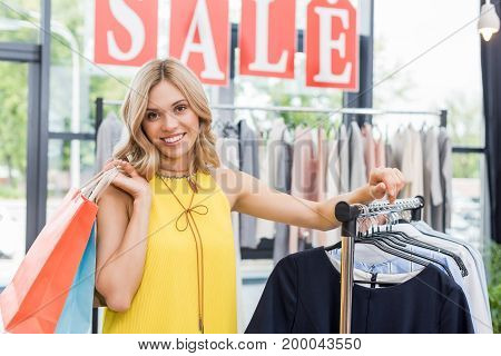 Beautiful Blonde Shopaholic Woman In Clothes Store