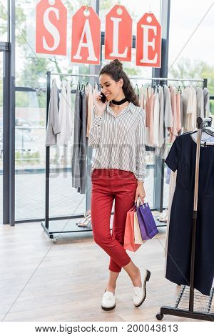 young beautiful woman in clothes store talking by phone