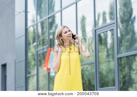 beautiful blonde woman on shopping talking by phone