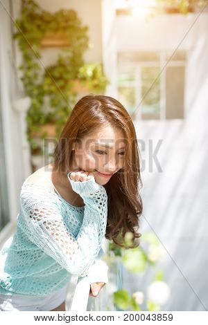 Carefree. Woman Relaxing On Balcony At Home