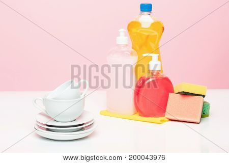 Several plates, a kitchen sponges and a plastic bottles with natural dishwashing liquid soap in use for hand dishwashing. Eco-friendly, toxin-free, green cleaning product. Dishwashing and cleaning concept.