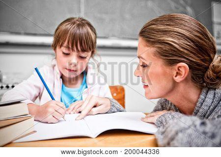 Schoolgirl writing with her smiling teacher in classroom