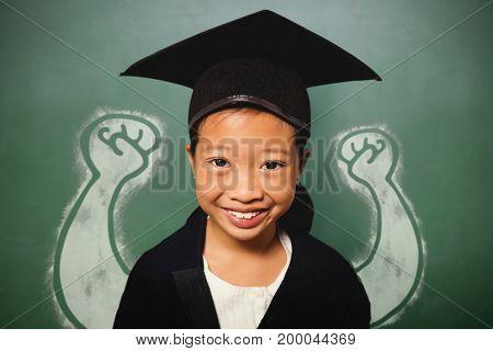 Portrait of smiling girl wearing mortarboard against green chalkboard