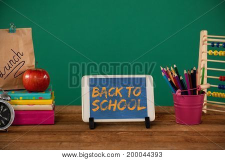 Graphic image of red back to school text against school supplies with digital tablet on wooden table