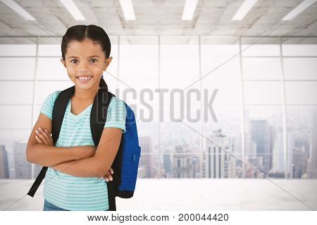 Portrait of smiling girl with arms crossed carrying bag against modern room overlooking city