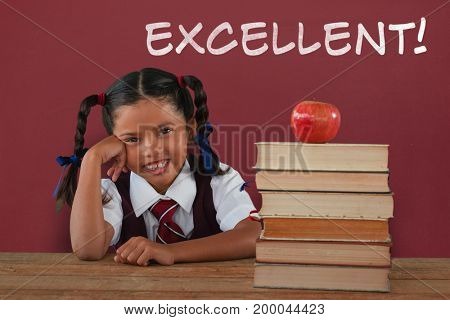Schoolgirl leaning by books and apple on desk against excellent text against white background