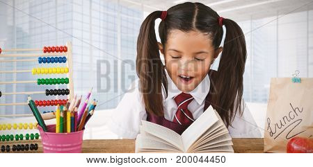 Schoolgirl reading book at desk against modern room overlooking city