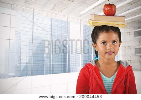Girl balancing books and apple on head against modern room overlooking city