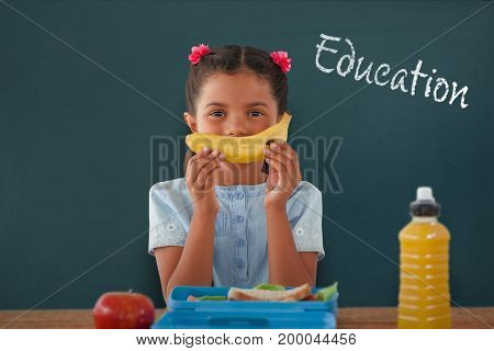 Girl holding banana at table against education text against white background