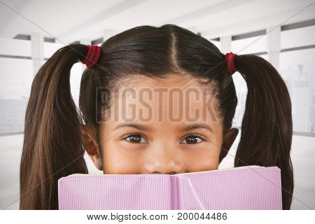 Schoolgirl covering mouth with book against windows overlooking city