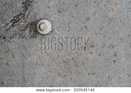 Grey concrete texture background with one white bolt