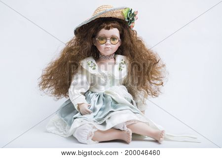 Portrait of a sitting ceramic porcelain handmade vintage doll with yellow glasses, curly long blond hair in an old linen dress with embroidery in wicker hat with green decoration on white background.