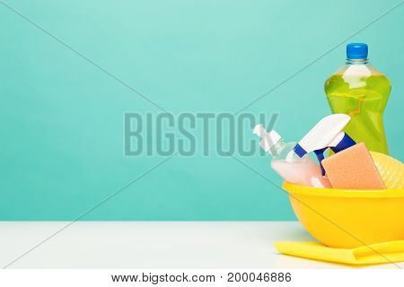 Various bottles with cleaning supplies on colored studio background