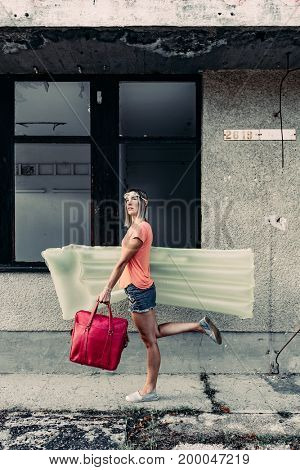 Silly image of woman walking with air mattress and red bag at abandoned city.