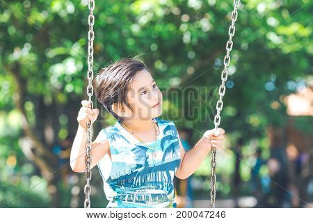 A Cute Asian Boy Is Playing Swings Happily.