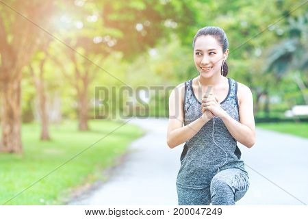 Fitness Women Are Exercising And Listening To Music From Her Mobile Phone In The Morning Garden.