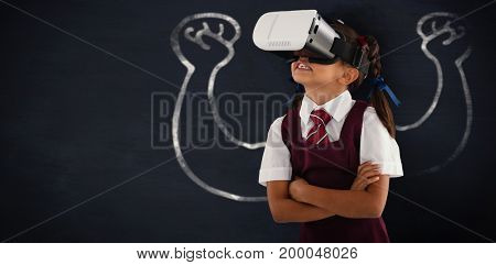 Schoolgirl wearing virtual reality headset enjoying with arms crossed against black background