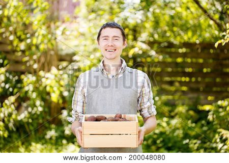 Photo of farmer with box of potatoes in summer garden