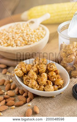 Corn Kernels In Wooden Plates And Popcorn With Caramel And Almond Cream On Wooden Table