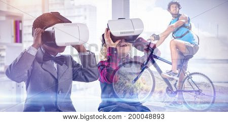 Fit man cycling on rocky terrain against children imitating business people wearing virtual reality headset