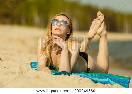 Summertime pleasures enjoying vacation concept. Woman in bikini sunbathing and relaxing on beach