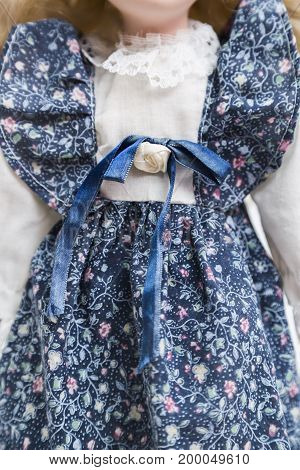 Ceramic porcelain handmade vintage doll with no face in old blue textile dress with gentle floral print decoration, in white shirt with knitted embroidery with blue silk bow with a rose.