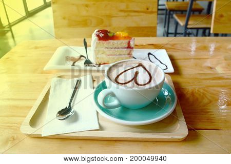 A Cup Of Coffee And Cake  On  Wooden Table With Yellow Light