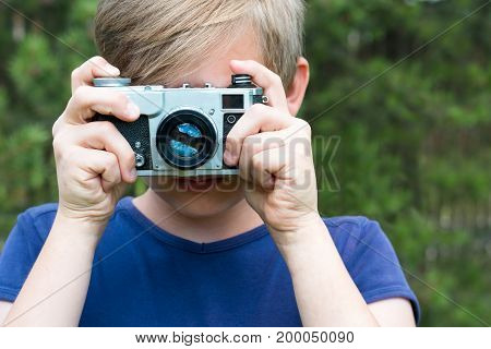 Teen is holding an old and vintage photo-camera. Outdoors. Close up.