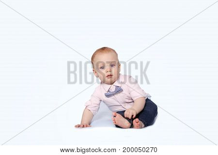 Cute infant boy in a pink shirt and a bow-tie sitting on the white background and looking at camera. Copy space.