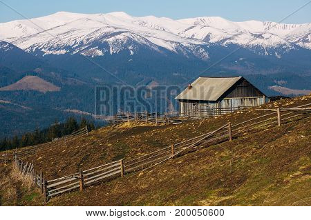 old wooden house in winter mountain background, landscape