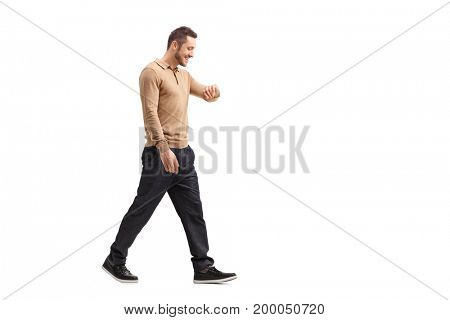 Full length profile shot of a young guy walking and looking at his watch isolated on white background