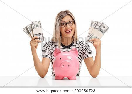 Cheerful woman behind a table with bundles of money and a piggybank isolated on white background