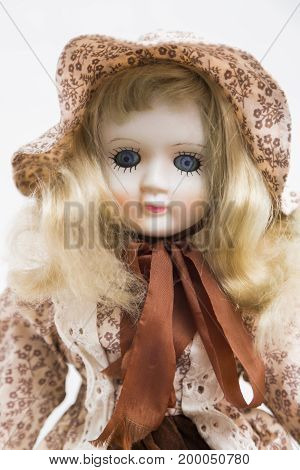 Portrait of ceramic porcelain handmade vintage doll with blue eyes, wavy blond hair in brown old linen textile dress with embroidery, floral print decoration in hat and silk bow on white background.