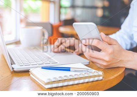 Business Woman Hand Holding A Mobile Phone And Working On A Laptop In An Office.