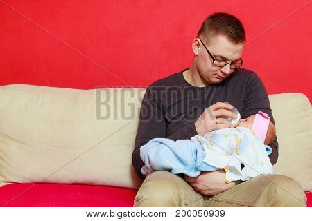 Parenting and love concept. Father holding and taking care of little newborn baby feeding milk from bottle.
