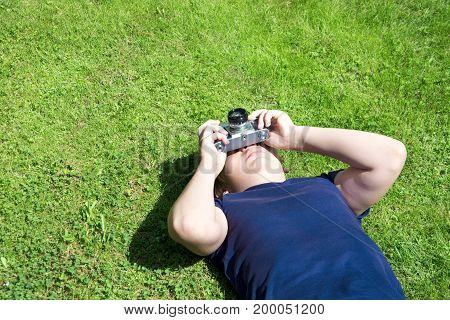 Teen is lies on green grass and takes shoot by old and vintage photo-camera. Outdoors. Copy space.