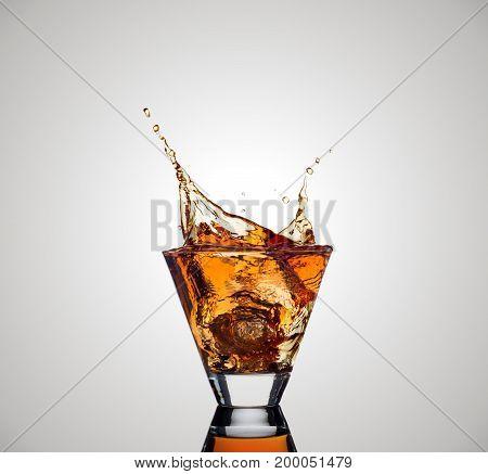 Whiskey splash out of glass on white background.