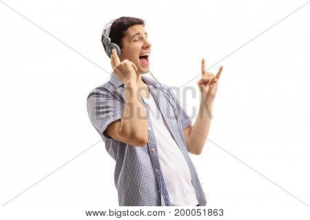 Young man listening to music on headphones and making a rock hand gesture isolated on white background
