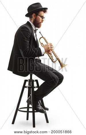 Profile shot of a trumpet player seated on a chair isolated on white background