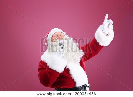 Santa Claus singing Christmas songs on color background