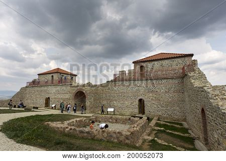 BELCHIN BULGARIA - SEPTEMBER 3 2016: Tourists walks arround partly reconstructed roman fortress Cari Mali Grad near town of Belchin 3 September 2016 Bulgaria.