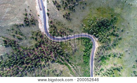 aerial view of a curved road in the forest